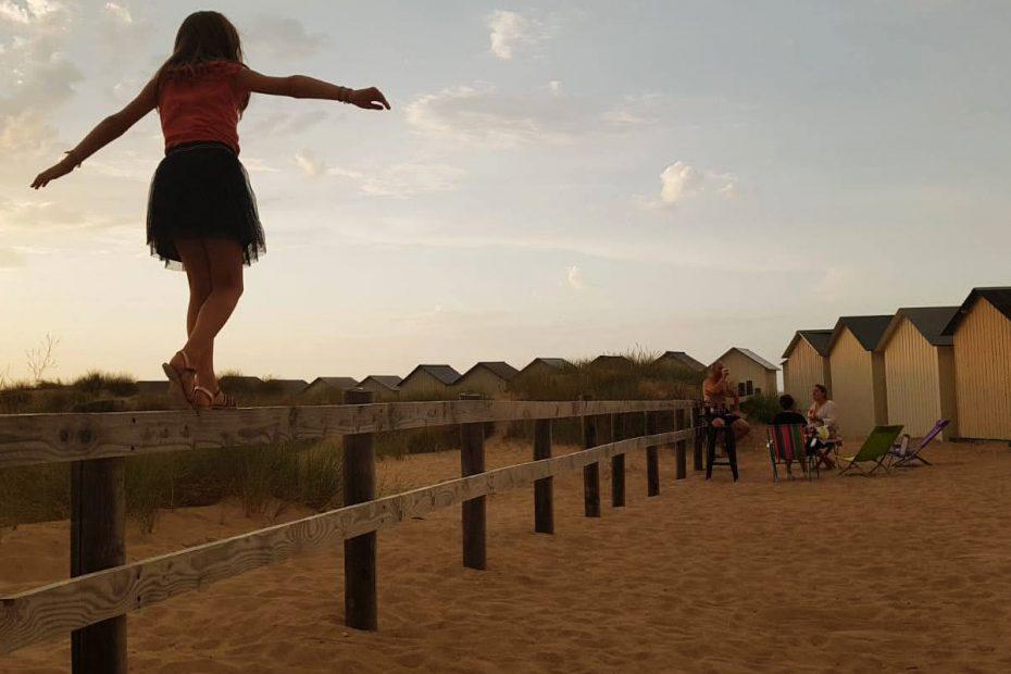 fillette en équilibre dans les dunes derrières les cabines de plage le temps d'un apéritif entre amis