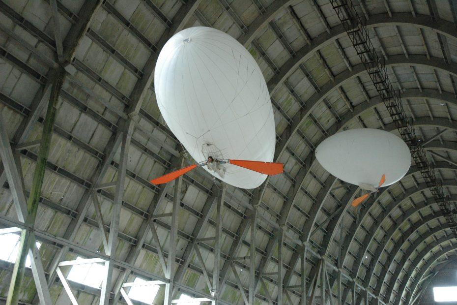 femme accrochée à un ballon dirigeable qui avance en battant des ailes